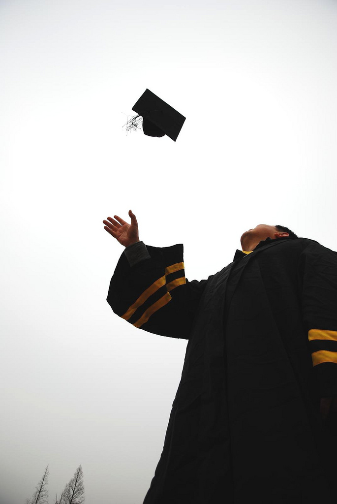 A student throwing their cap in the air on graduation day.