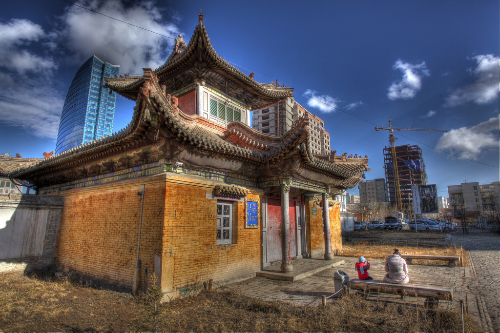 A traditional house in Mongolia alongside modern buildings.