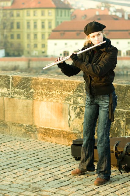 Girl busking with a flute in Prague