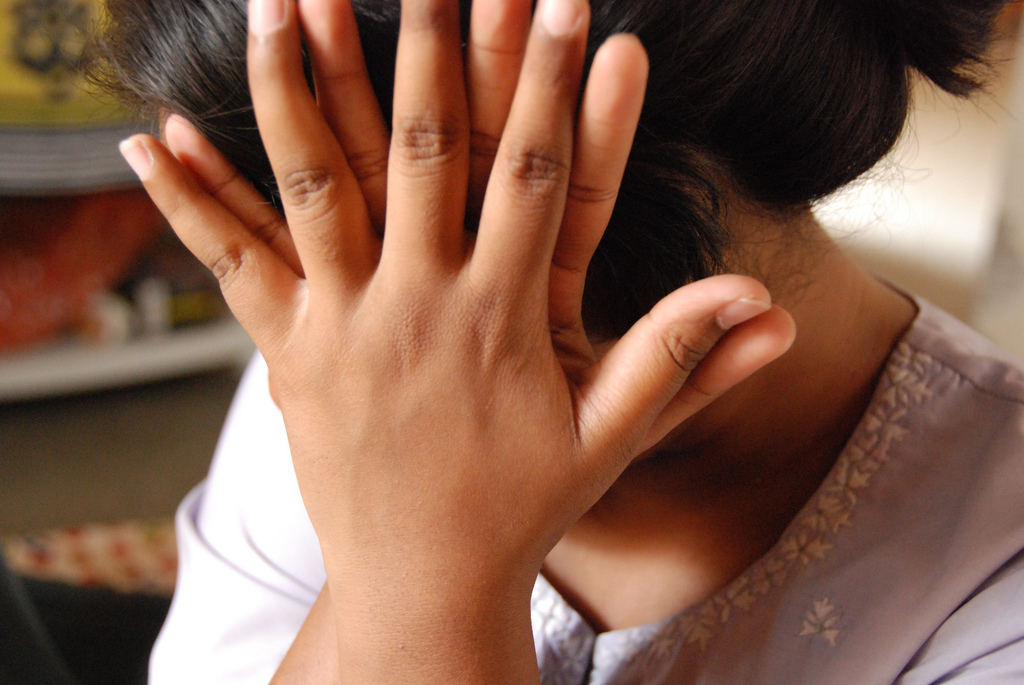 A shy girl covering her face with her hands.