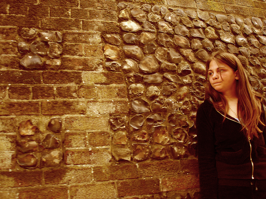 A girl standing by a stone wall, looking anxious.